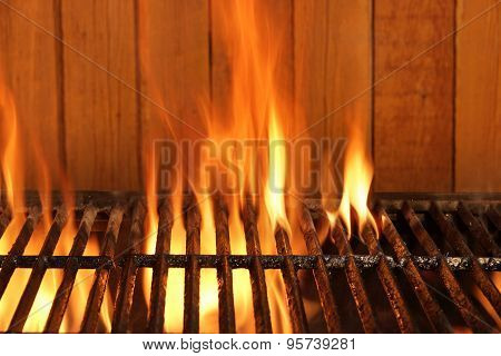 Flaming Bbq Charcoal Cast Iron Grill And Wood Background