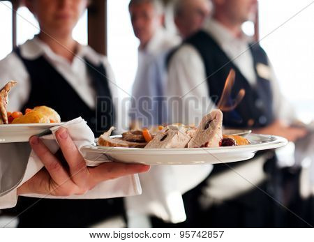 Waiters carrying plates with meat dish at a wedding