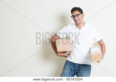 Courier delivery service concept. Happy Indian man holding brown boxes, standing on plain background with shadow. Asian handsome guy model.