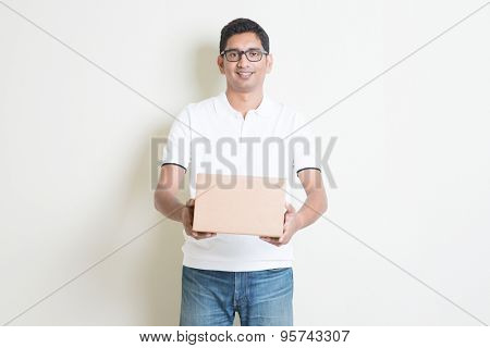 Courier delivery service concept. Indian man received a brown box, standing on plain background with shadow. Asian handsome guy model.