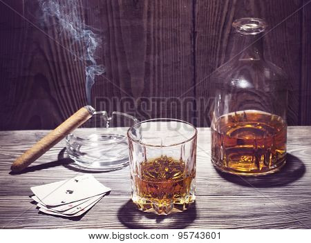 Cognac and cigar burning on a wooden table