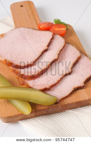 slices of roasted pork on wooden cutting board and white place mat