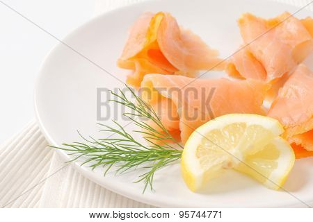 close up of smoked salmon slices on white plate