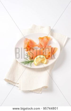 slices of smoked salmon on white plate and place mat