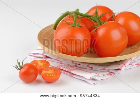 close up of fresh tomatoes on bamboo plate and checkered dishtowel