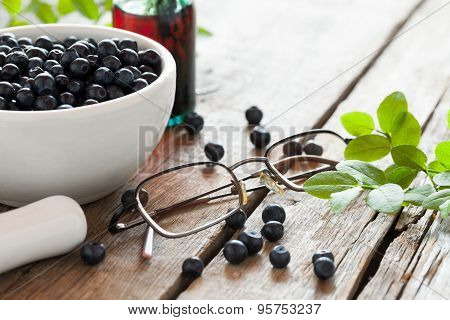Bowl With  Blueberries, Glasses And Bottle Of Tincture On Wooden Table.