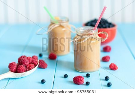 Fresh rastberry, blueberry and banana juice in jam jar on light blue wooden table, apple protein coc