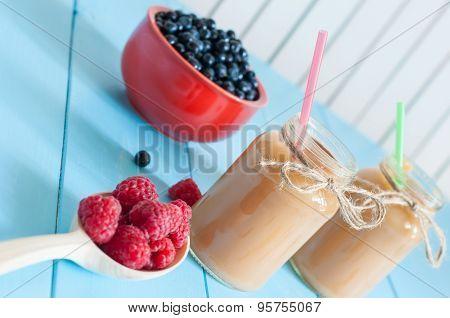 Homemade apricot smoothie in jam jar on light wooden background. Fresh rastberries, blueberries at b
