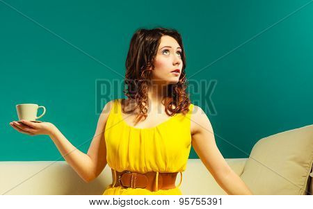 Woman Sitting On Sofa Holds Coffee Cup