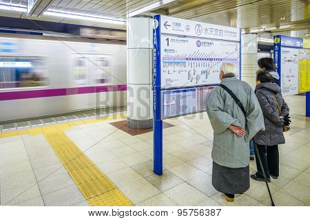 TOKYO, JAPAN - JANUARY 3, 2013: Riders view a subway map as a train approaches at Suitengumae Station.  The station is on the Tokyo Metro Hanzomon Line.