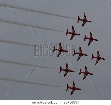 Red Arrow Display Team in dark sky