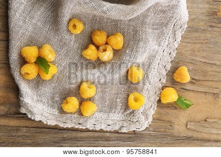 Yellow raspberries on sackcloth on wooden table, closeup