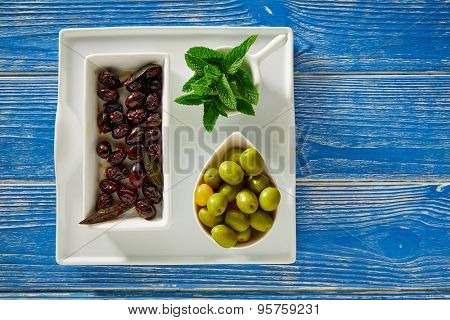 Mediterranean pickles tapas black olives and mint leaves on blue wood table