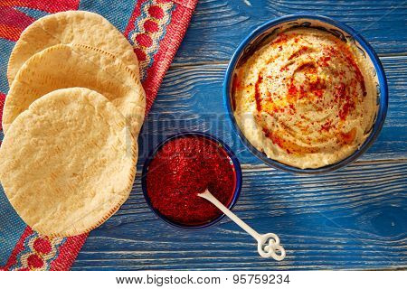 Hummus with pita bread and red pepper powder on blue Mediterranean wood table
