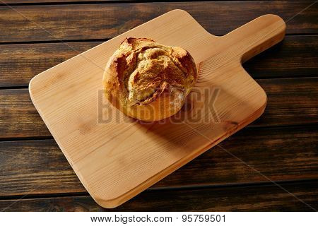 Bread round loaf on wooden board in rustic wood table