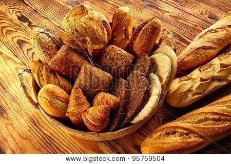 Bread fresh varied mix on golden rustic wood in basket