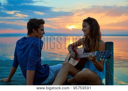 Couple playing guitar in sunset pier at dusk beach happy together