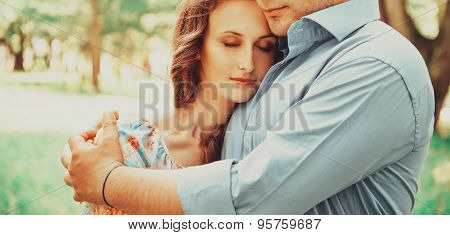 Man Embracing Woman With Closed Eyes Outdoor
