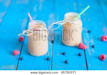 Milkshake or banana smoothie in a mason jar with straws on blue rustic wood background