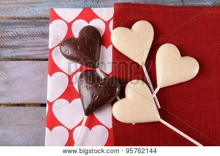 Chocolate heart shaped candies on sticks on red napkin, closeup