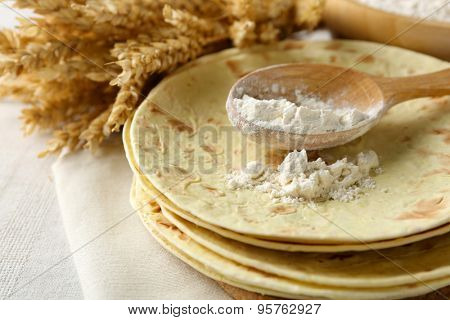 Stack of homemade whole wheat flour tortilla on plate, on light background