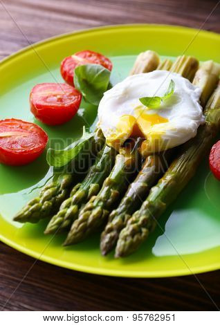 Roasted asparagus with tomatoes and poached egg on plate on table close up