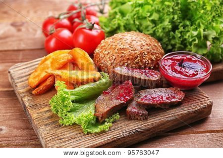 Beef with cranberry sauce, roasted potato slices and bun on cutting board, on wooden background