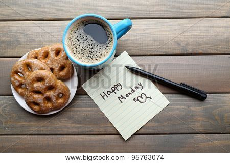 Cup of coffee with fresh cookies and Happy Monday massage on wooden background