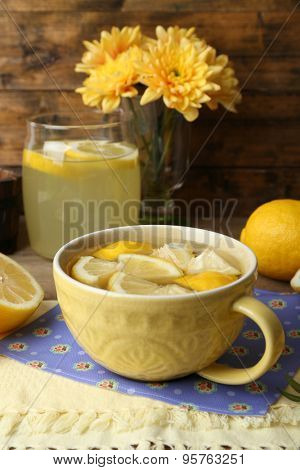 Still life with lemon juice and sliced lemons on wooden table with napkin, closeup