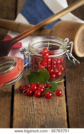 Redcurrant in jam glass and on rustic table with kitchen utensils, vertical