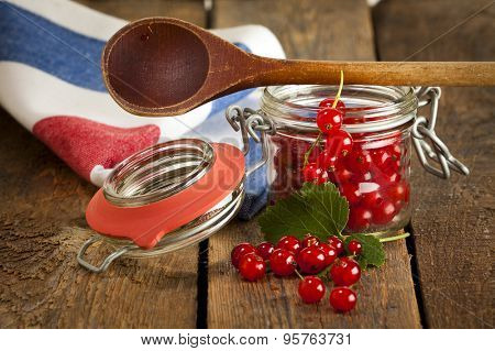 redcurrant in jam jar with kitchen spoon and towel on wooden table