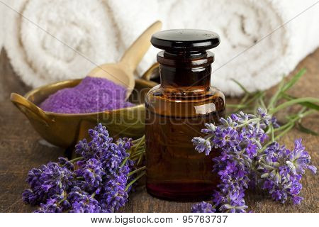 Lavender flowers, apothecary bottle, bowl of bath salt and towels