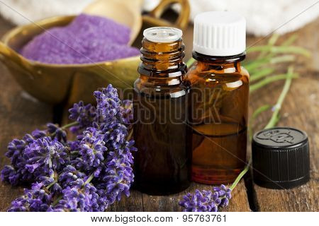 Bottles of aromatherapy essence and bath salt with lavender flowers closeup