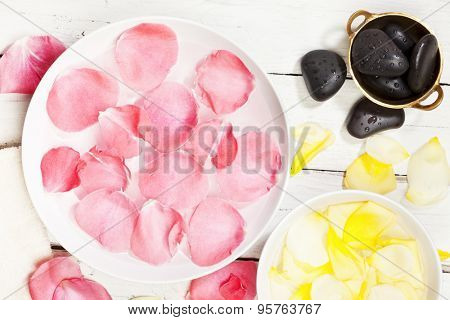 Bowls with pink and yellow rose petals and black massage stones
