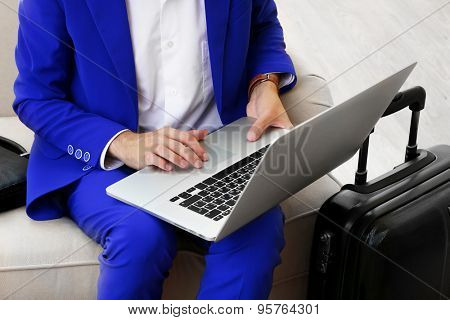 Business man with suitcase and laptop sitting on sofa in hall