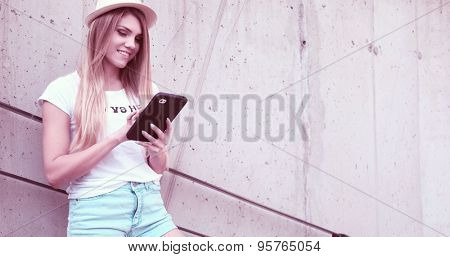 Pretty Young Woman Wearing Trendy Outfit, Using her Tablet Computer While Leaning Against the Building Wall