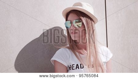 Close up Stylish Young Attractive Woman Wearing Hat and Sunglasses, Leaning Against the Wall and Looking Into Distance.