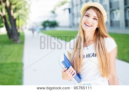 Cheerful Blond Student Teen Girl in Casual Outfit, Holding Books and Smiling at the Camera While Standing at the Outdoor Walkway.