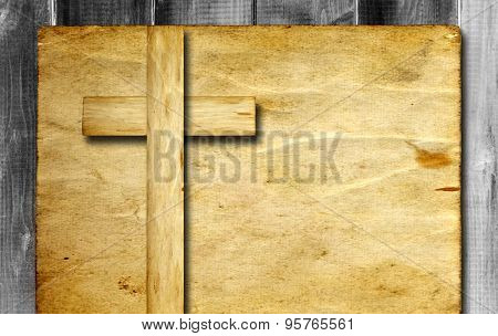 Vintage old grungy paper banner with a Christian religious cross over ancient wood background for religion or faith designs