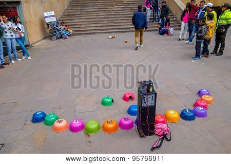 Unidentify crowd watching street guinea pig gambling were animal goes into the colorful upturned pla