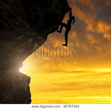 Silhoutte of girl climbing on rock at sunset