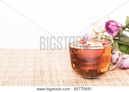 transparent cup of tea on wilted bouquet background