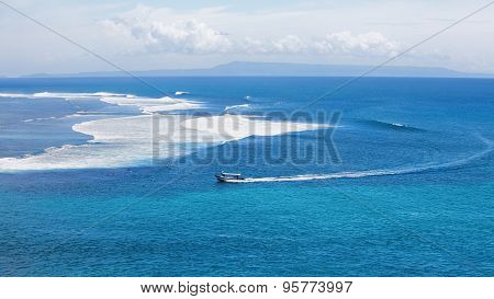 Clear Blue Ocean With Boat And Surfers On Big Waves
