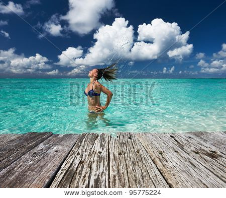 Woman splashing water with her hair in the ocean