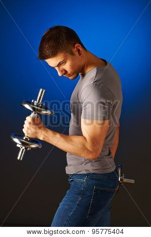 Man working out with dumbbells on blue background