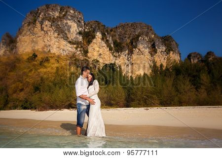 Bride And Groom At Sea Edge Against Cliffs