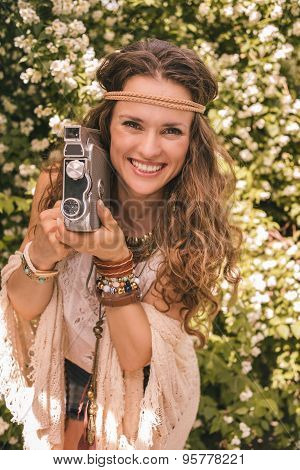 Happy Boho Young Woman Among Flowers With Retro Camera