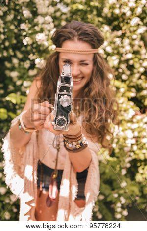 Closeup On Boho Young Woman Among Flowers Using Retro Camera