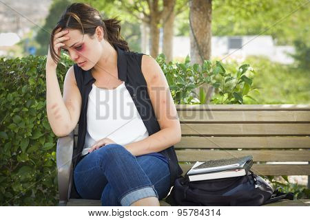 Sad Bruised and Battered Young Woman Sitting on Bench Outside at a Park.