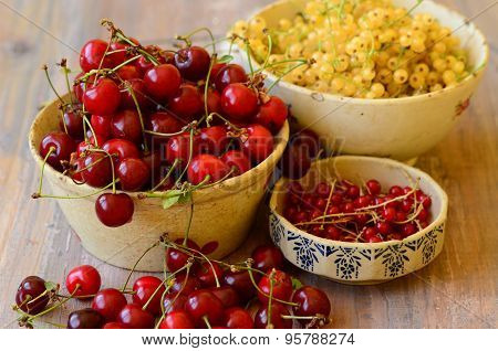 Cherries, currants in three vintage bowls on wooden background.